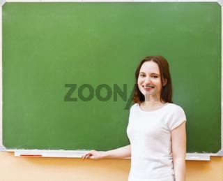 Student girl standing near clean blackboard in the classroom