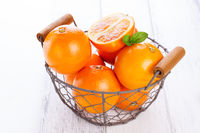 Fresh juicy summer blood oranges in a vintage basket with mint leaf on wooden table on a white background