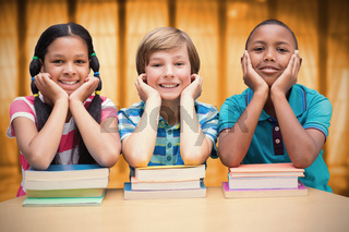 Composite image of cute pupils looking at camera in library