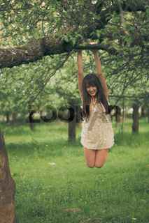 Girl clings to a tree branch