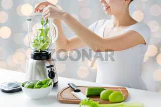 close up of woman with blender and vegetables