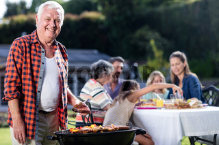 Senior man at barbecue grill while family having lunch in background
