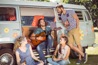 Hipster playing guitar for his friends