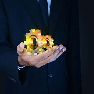 businessman showing gears cogs to success concept
