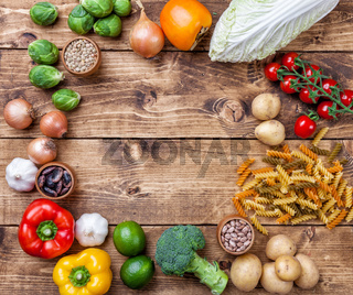 Fresh and healthy organic vegetables and food ingredients on wooden background
