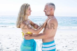 Happy couple standing by the sea and smiling at each other
