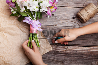 Making a rustic bouquet from gillyflowers and alstroemeria on old wooden background with wooden heart and scissors with paper