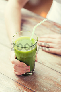 close up of woman hands with green juice