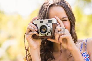 Pretty brunette in the park using retro camera