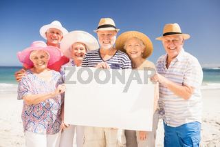 Smiling senior friends holding blank paper