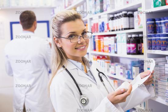 Pharmacist taking medicine from shelf
