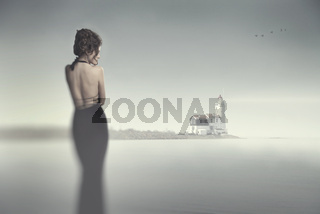 Girl in evening dress standing on the beach in heavy fog and looking at the fog and flying birds.