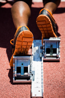 Feet of an athlete on a starting block about to run