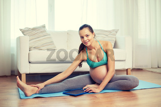 happy pregnant woman with tablet pc exercising