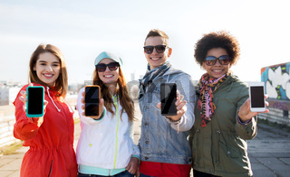 smiling friends showing blank smartphone screens