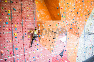 Fit woman rock climbing indoors