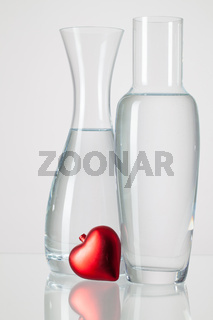 Two vases with clean water and red heart