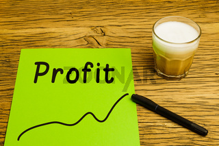 Profit written on green paper with graph. Marker and coffee on desk.