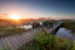 misty sunrise over wooden path on lake