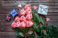 Roses and gift box over old wood background