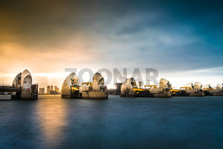 Thames Barrier, with light breaking over Canary Wharf in distance, River Thames, London, United Kingdom