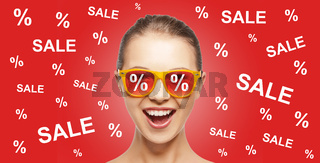 happy teenage girl in shades with sale signs