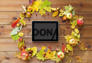 tablet pc with autumn leaves, fruits and berries