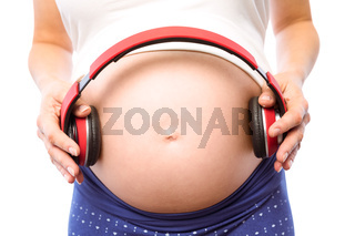 Pregnant woman holding earphones over bump