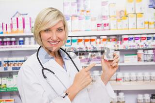 Smiling doctor pointing a drug bottle