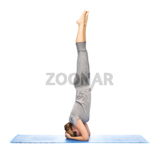 woman making yoga in headstand pose on mat