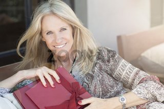 Cute middle age woman with gift in outdoors
