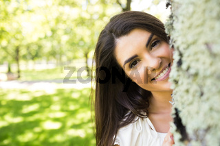 Portrait of smiling woman behind tree trunk