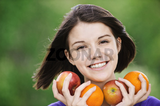 young merry woman holding fruits