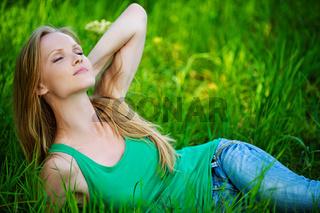 Portrait young woman lying green grass