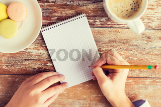 close up of hands, notebook, coffee and cookies