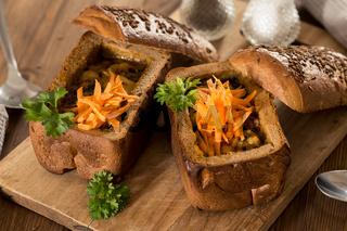 Fresh pea soup in bread bowl on a wooden desck