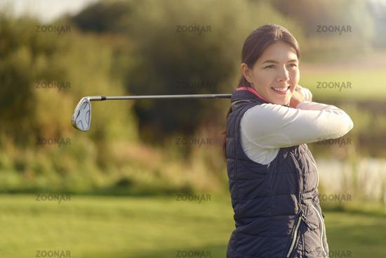 Lächelnde Golferin nach einem Schlag