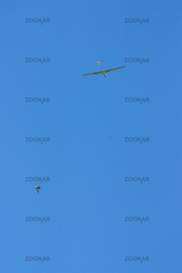 Segelflugzeug mit Windenfallschirm am blauen Himmel