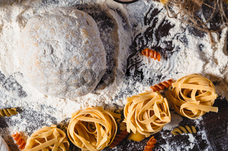 Pasta on dark wooden background with dough, eggs, oil and flour close-up macro