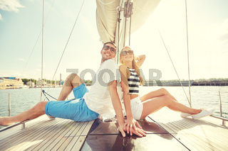 smiling couple sitting on yacht deck
