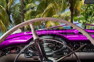 Kuba Innenansicht eines pinkfarbenen Oldtimers mit Palmen und Blick auf das Meer