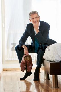 Geschäftsmann sitzt mit Schuhen in Händen