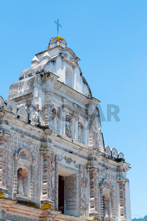 Big White Church With stone Carvings in front of blue sky