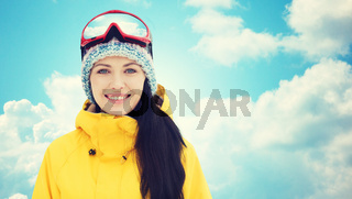 happy young woman in ski goggles over blue sky