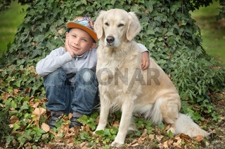 little cute boy playing with his dog in the park