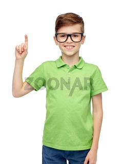 happy boy in eyeglasses pointing finger up