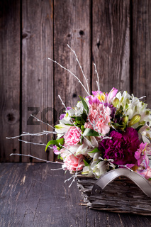 Bouquet from gillyflowers and alstroemeria in the basket on old wooden background