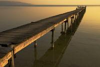 Der Tag geht zu Ende, letzte Sonnenstrahlen am Bootssteg des Sees