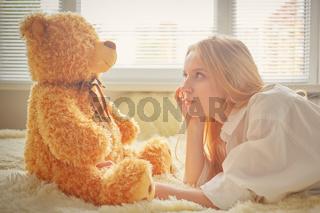 girl sitting with teddy bear