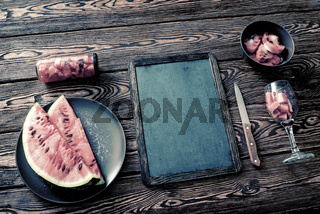 Chalkboard mockup on desk with watermelon. Top view.